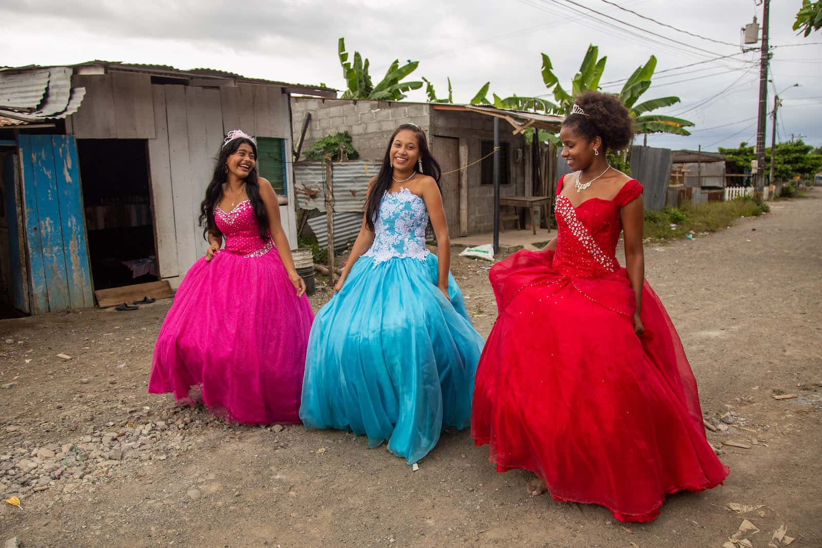 Three girls in formal wear walk down a dirt road.