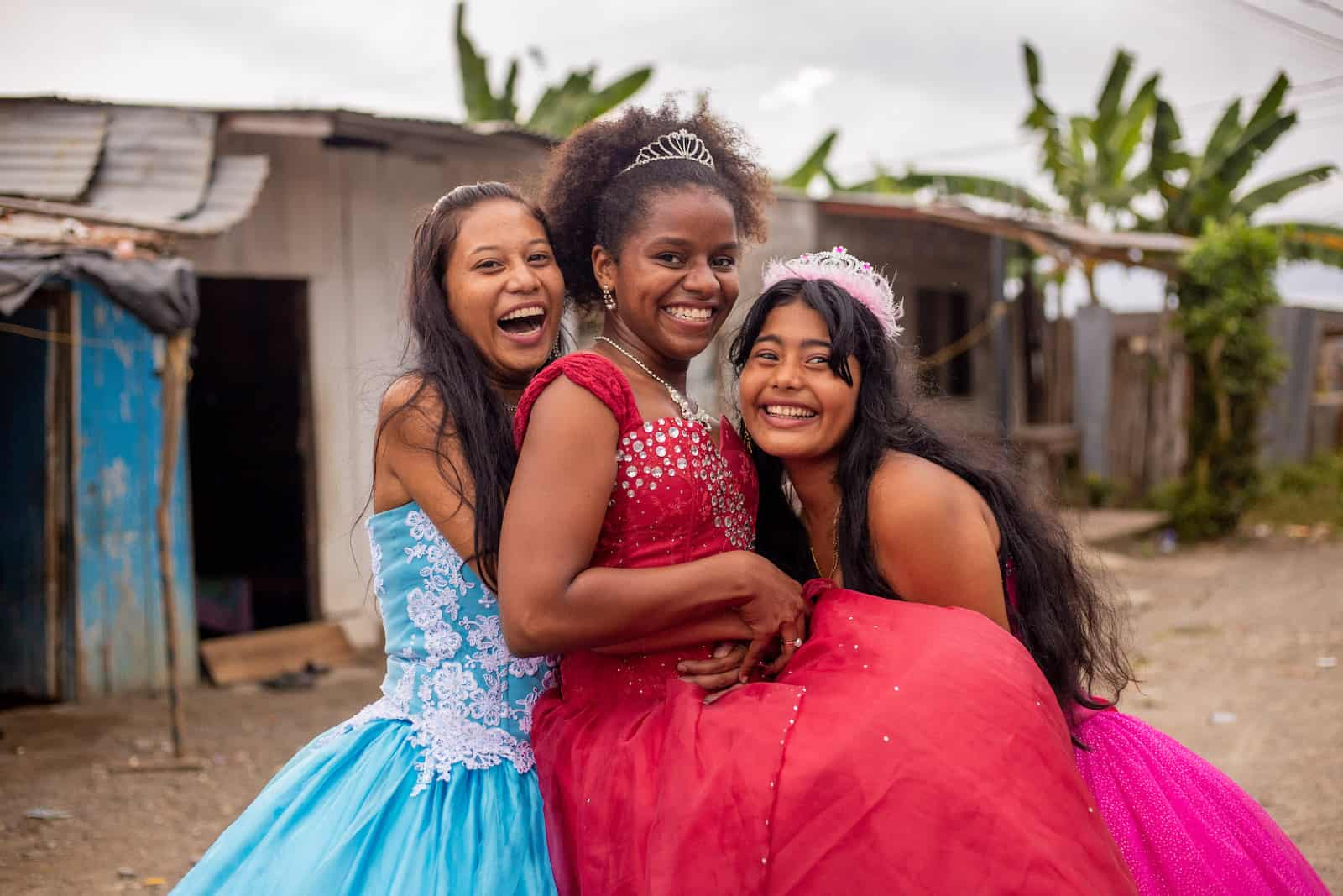 Three teenage girls celebrating a birthday tradition, the Quinceañera, in ballgowns hug, smiling and laughing.