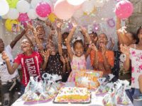 A group of children through confetti in the air, standing in front of a table with a birthday cake on it.