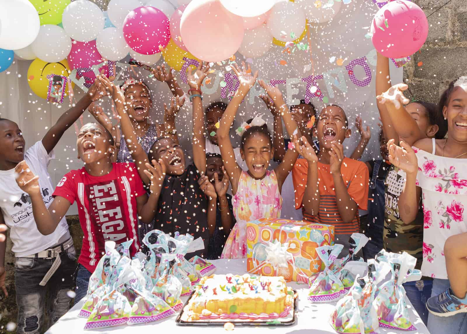 A group of children throw confetti in the air, standing in front of a table with a birthday cake on it.