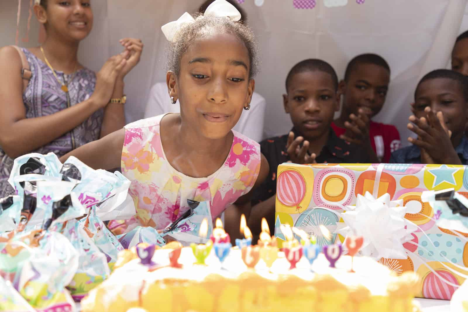 A girl leans over a birthday cake, blowing out the candles.