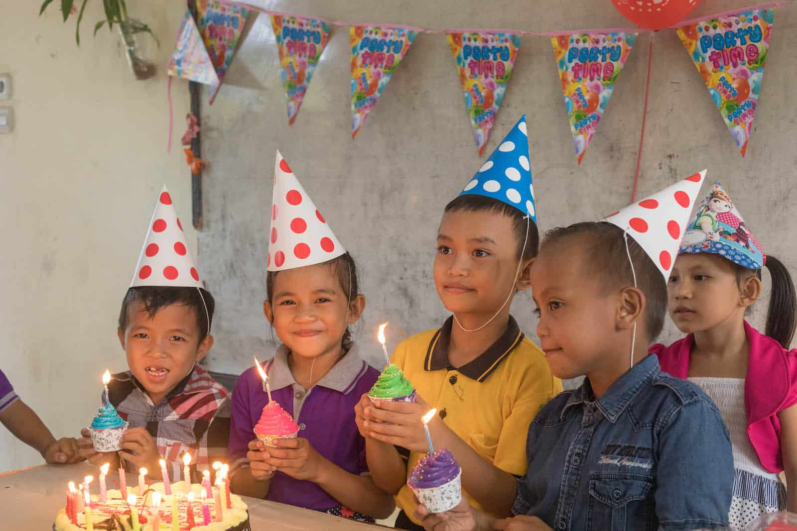 A group of children hold cupcakes, wearing birthday hats and standing in front of a lit birthday cake.