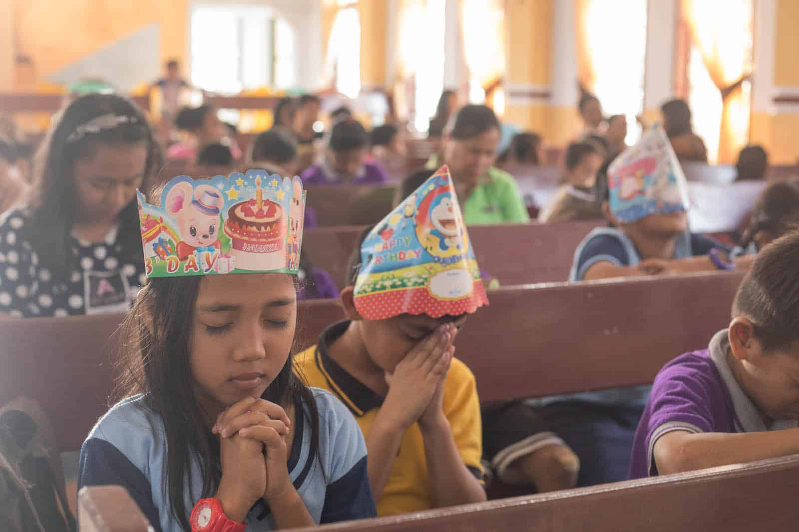 Two children wearing birthday party hats pray, sitting in pews in a church.