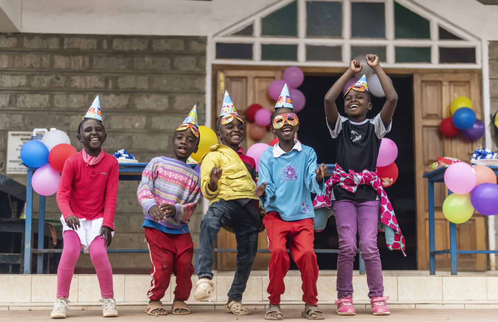 A group of children wearing party hats and party masks smile and dance outside a church.