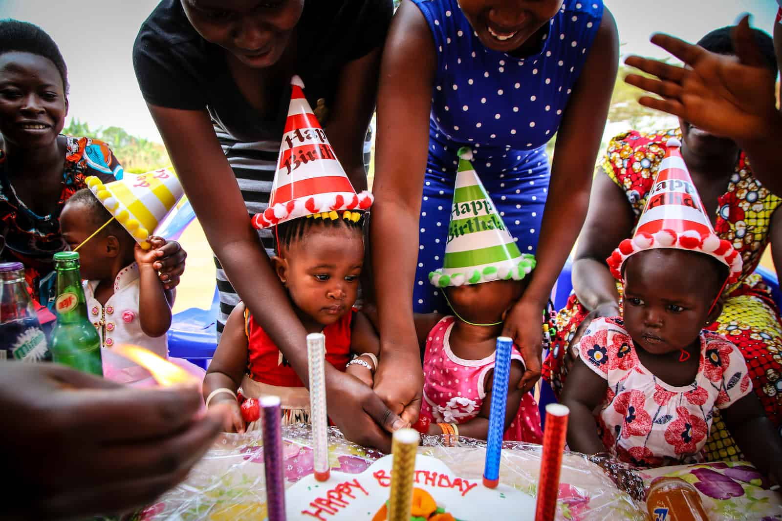 Three babies wearing birthday hats sit in front of a birthday cake.