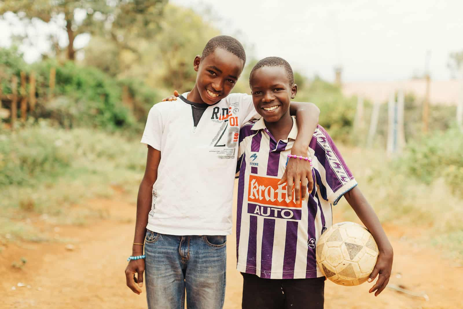 Two boys smile, one holding a soccer ball.