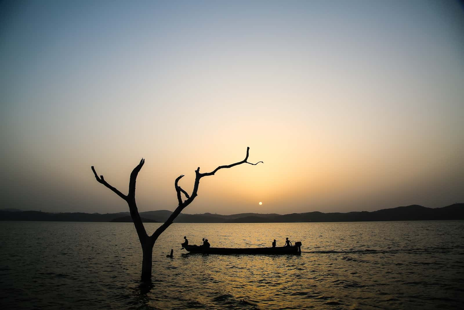 A canoe silhouetted at sunset on a lake.