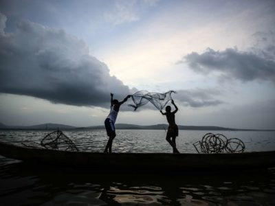 The silhouette of two people throwing a fishing net into a lake.