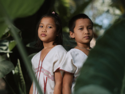 Two girls in white and red shirts stand amidst foliage, looking somber.