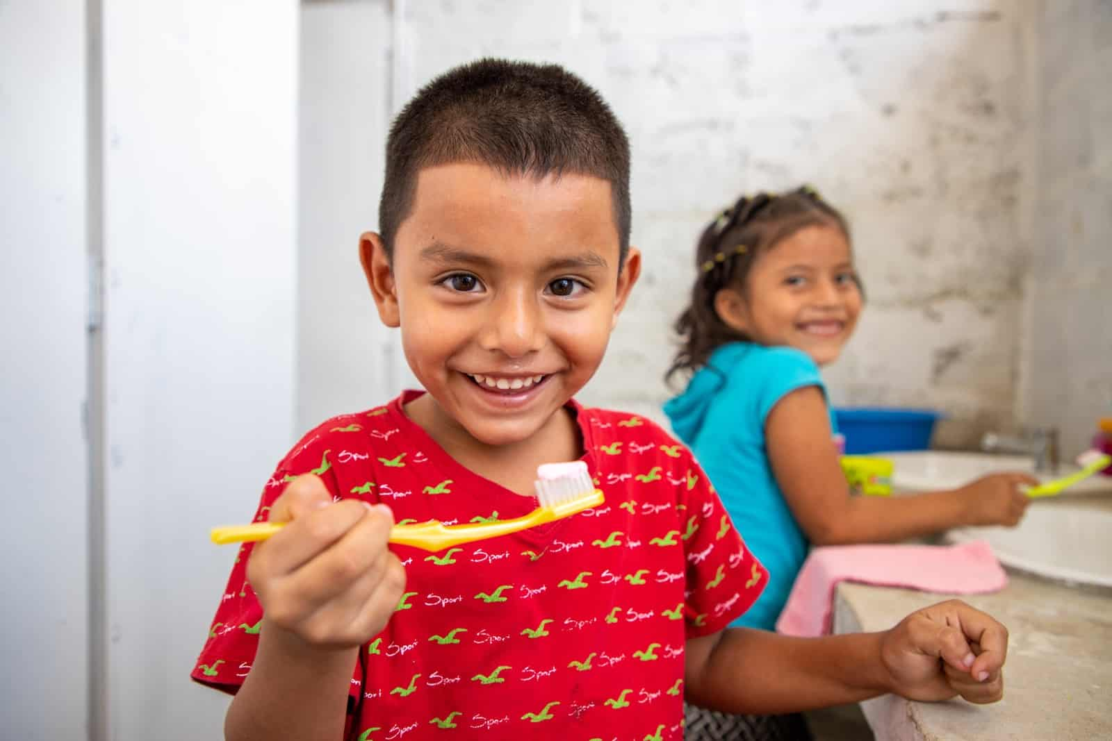 A boy in a red shirt holds up a toothbrush and smiles.