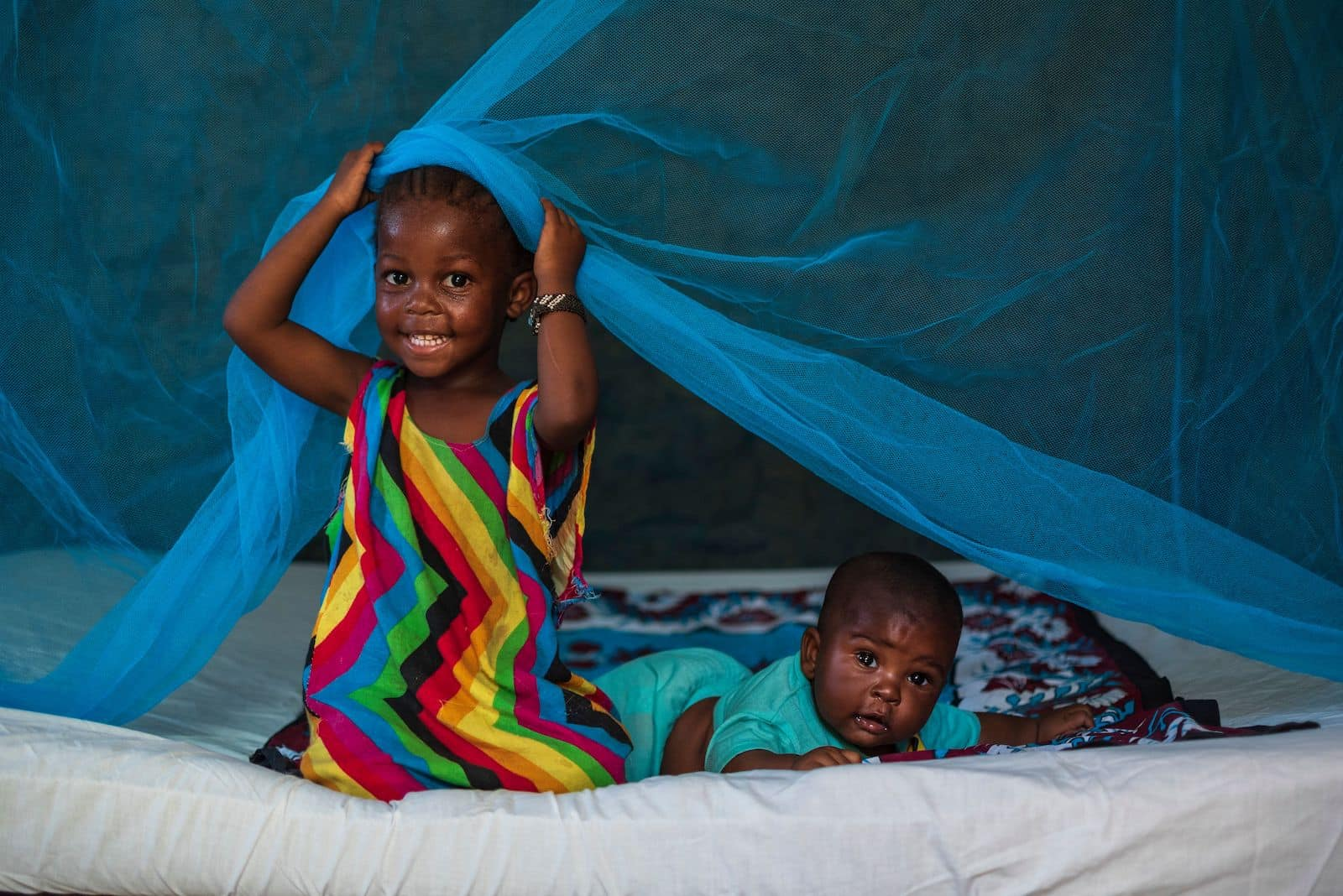 A girl and a baby sit on a bed with a malaria net on it.