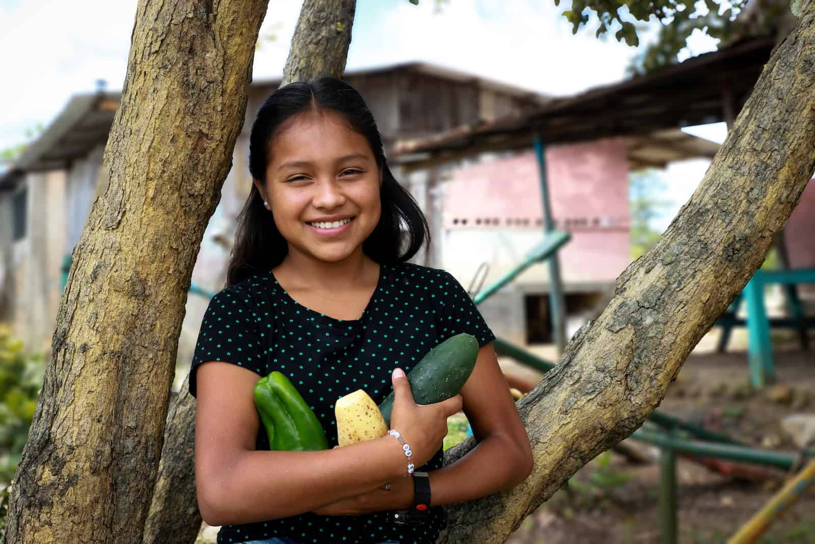 A girl leans against a tree, holding vegetables.