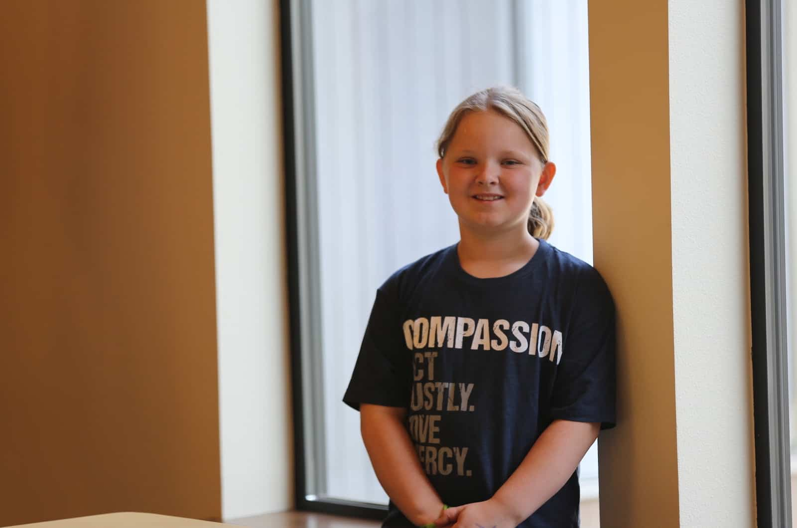 A girl in a T-shirt that says Compassion leans against a wall.