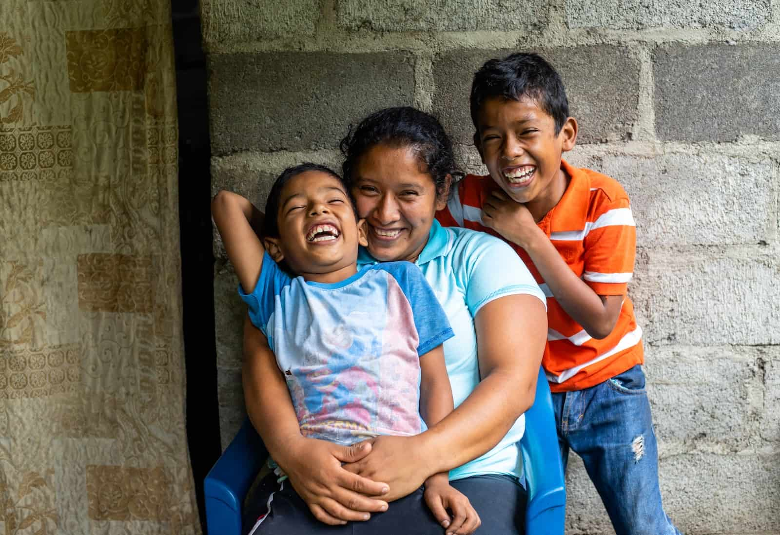 A woman holds a boy in her lap and a boy stands behind them, smiling.