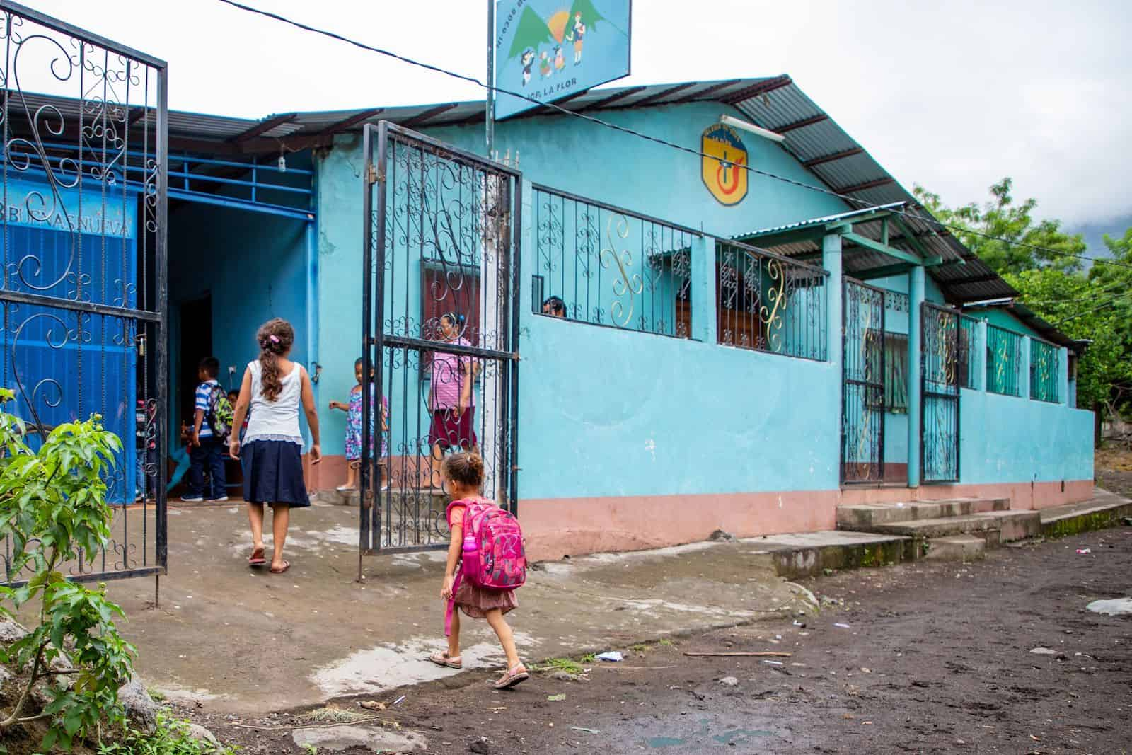 Children walk into a turquoise child development center where people were impacted by Nicaragua unrest.