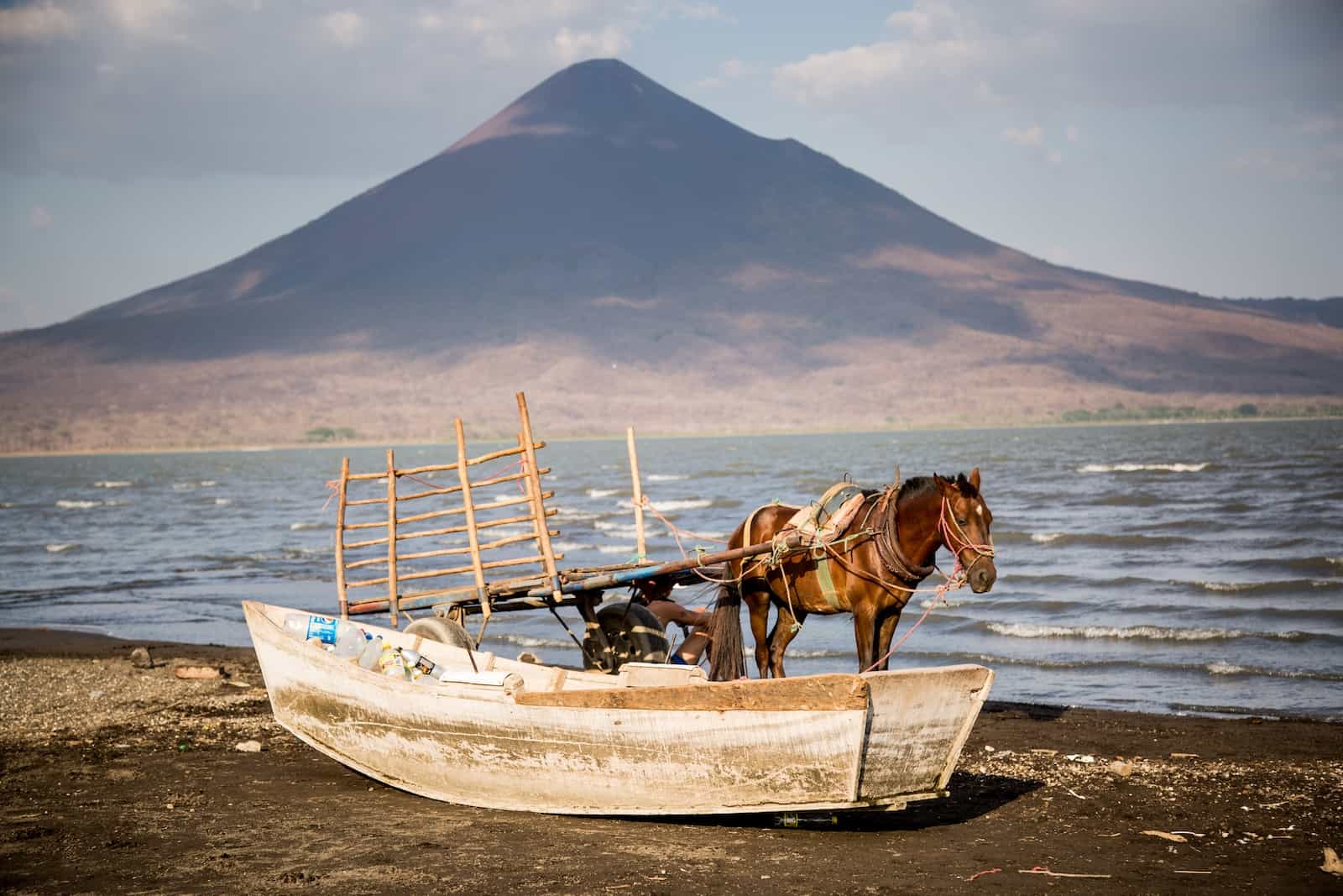 A horse stands next to a boat in front of a lake and volcano where tourism is down after Nicaragua unrest.