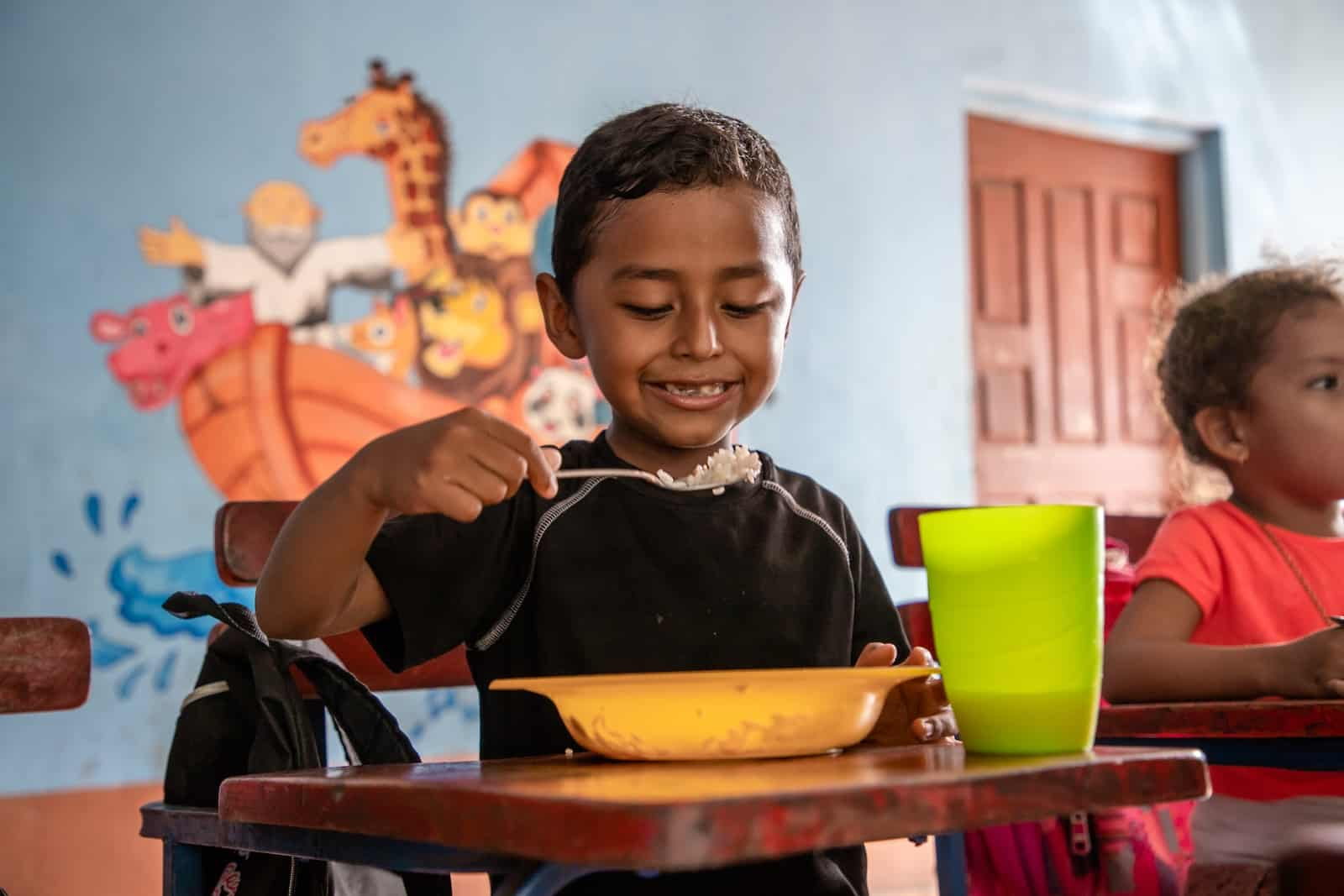 A boy sits at a desk, eating a bowl of food.