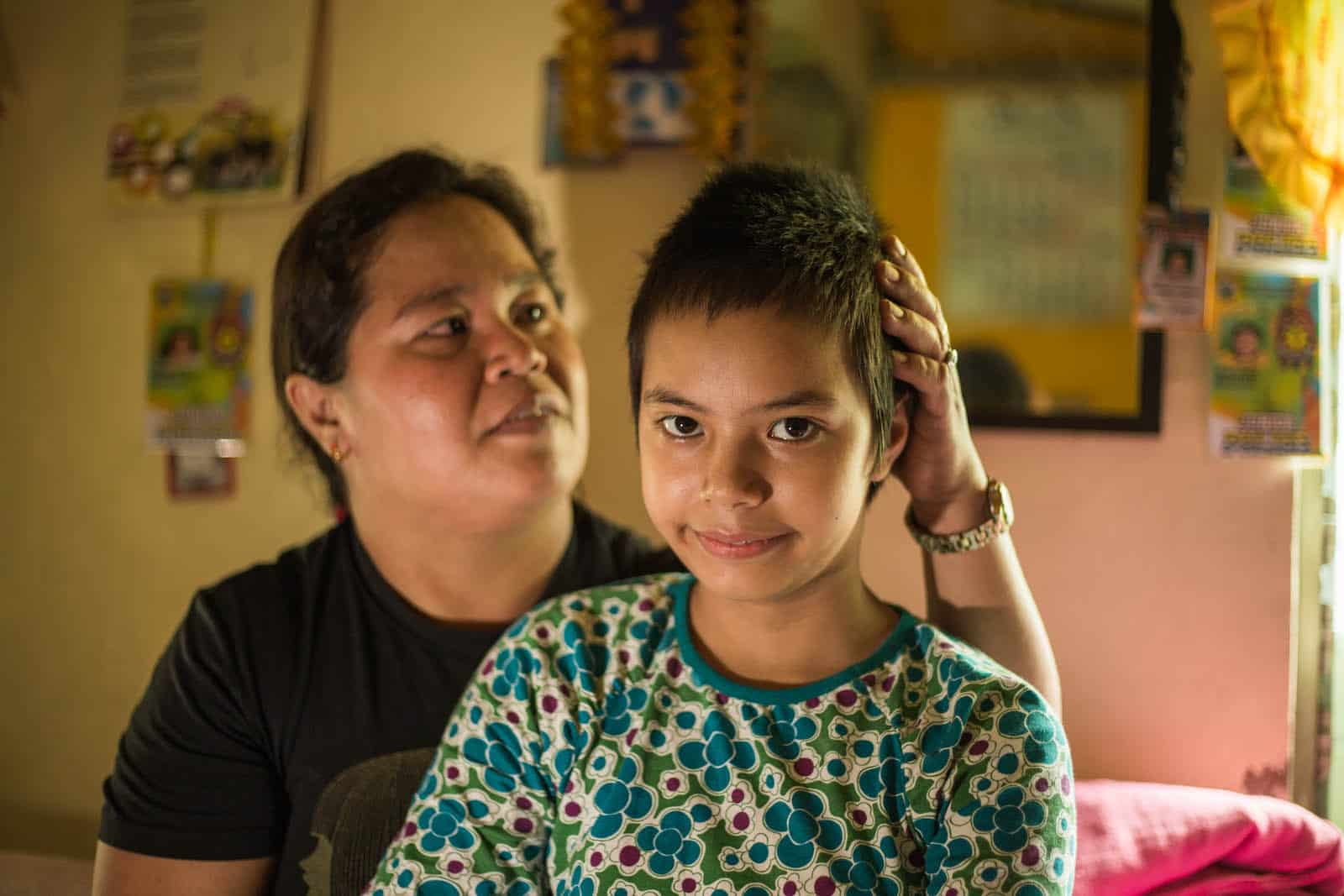 A girl with short hair sits in a room with her mother behind her.