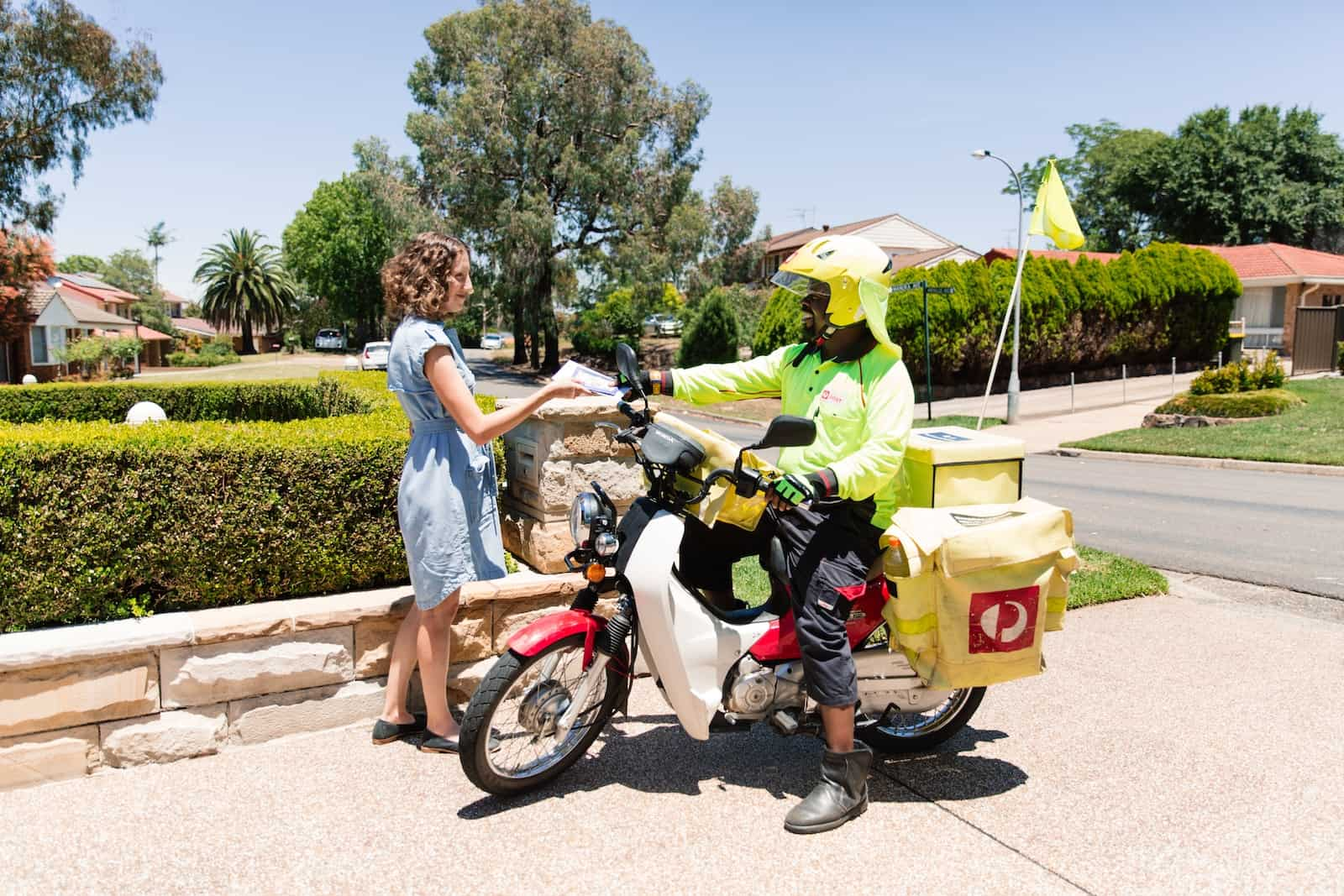 A mailman on a motorcycle hands a letter to a woman.