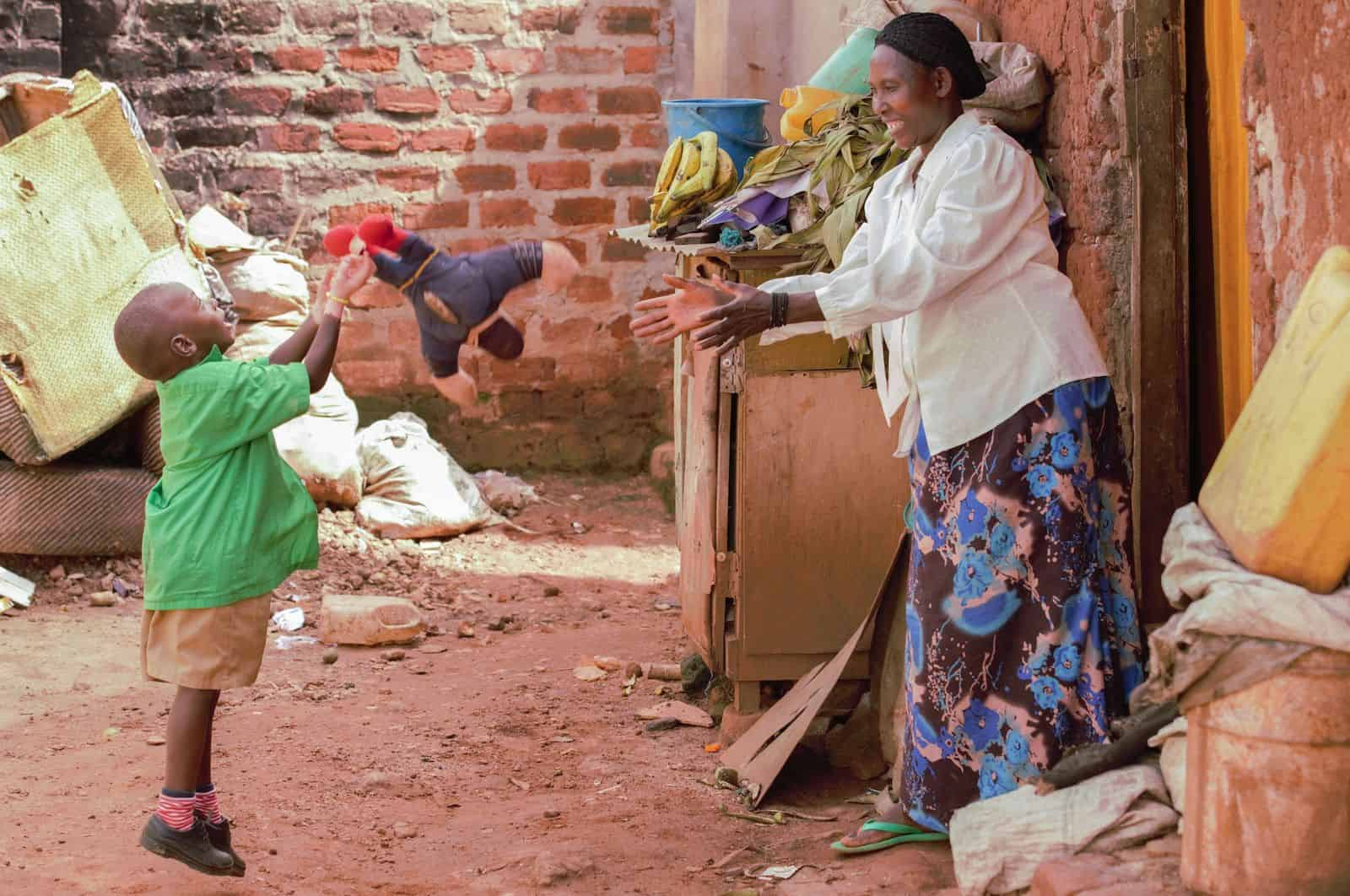 Waardenburg Syndrome Pictures: a boy with partial albinism tosses a toy outside a home to an older woman.