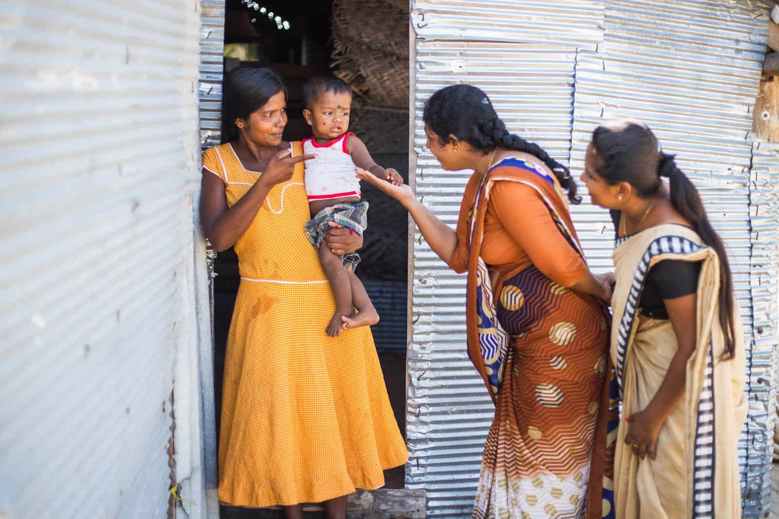 Three women stand outside of a metal sheet home, one holding a baby.