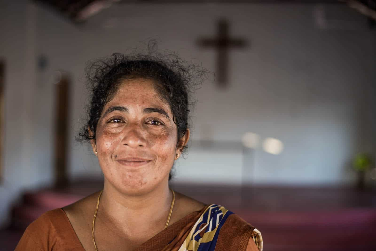 A woman who fights maternal suicide wears a brown dress standing in a church.