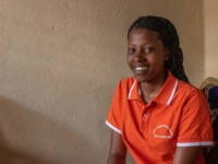 A young woman in an orange shirt smiles.