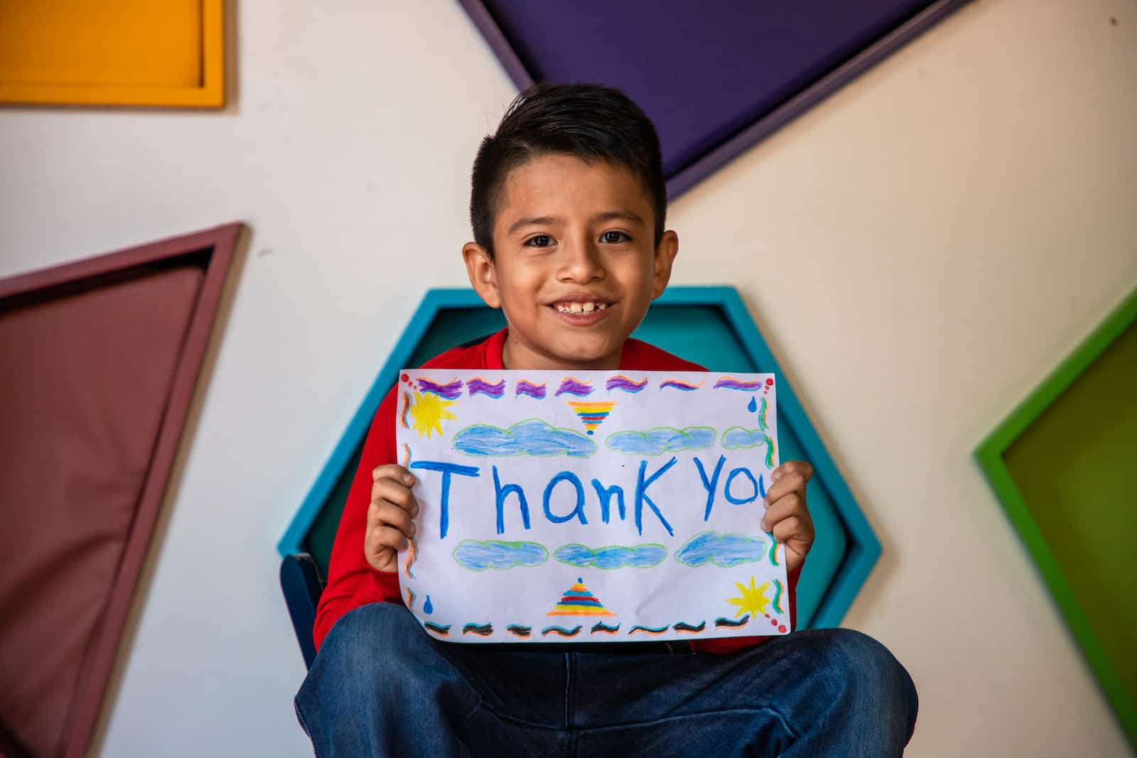 A boy holds a sign that says thank you