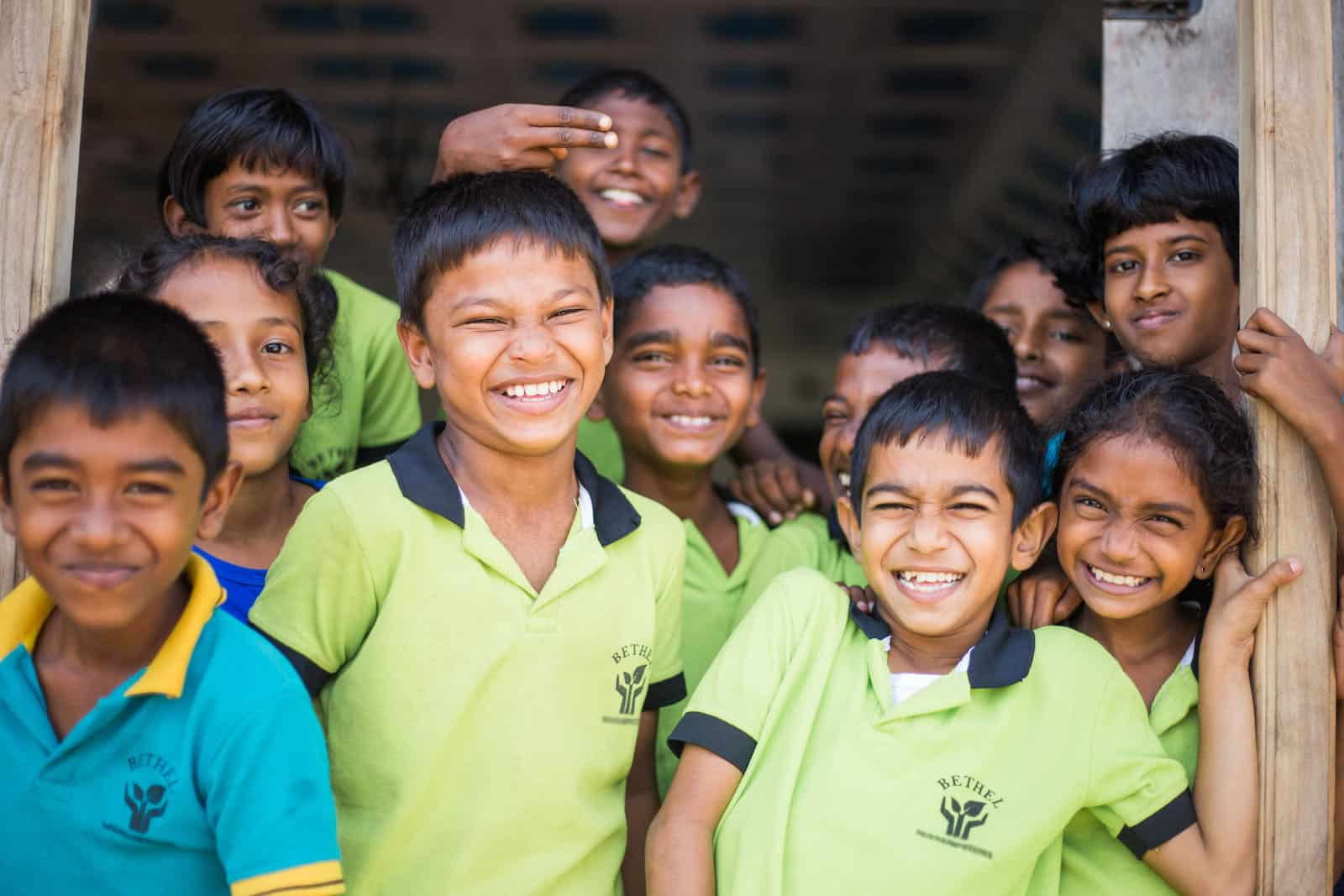 A group of children in lime green shirts smile at the camera.