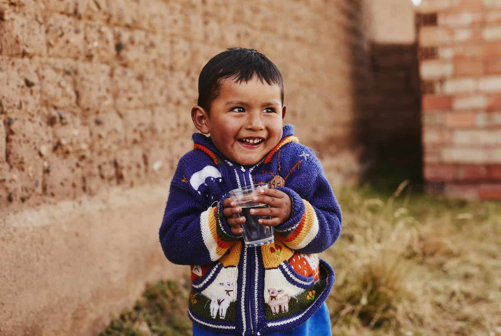Kids Around the World: A boy in a blue sweater holds a glass of water.