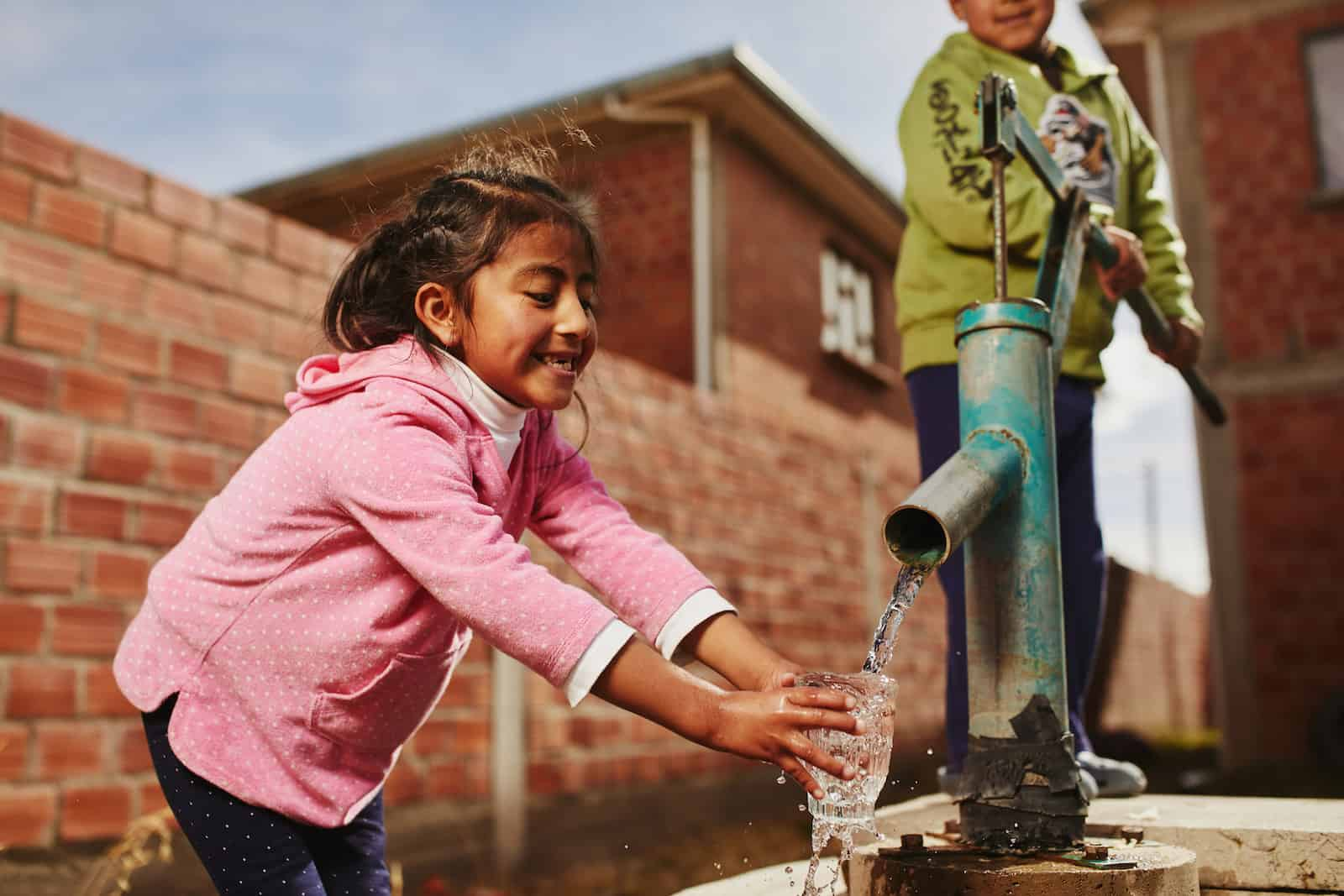 Kids Around the World: A girl gets water from a pump while a boy pumps.