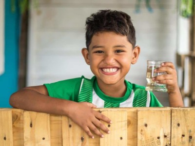 A boy stands at a fence holding a glass of water.