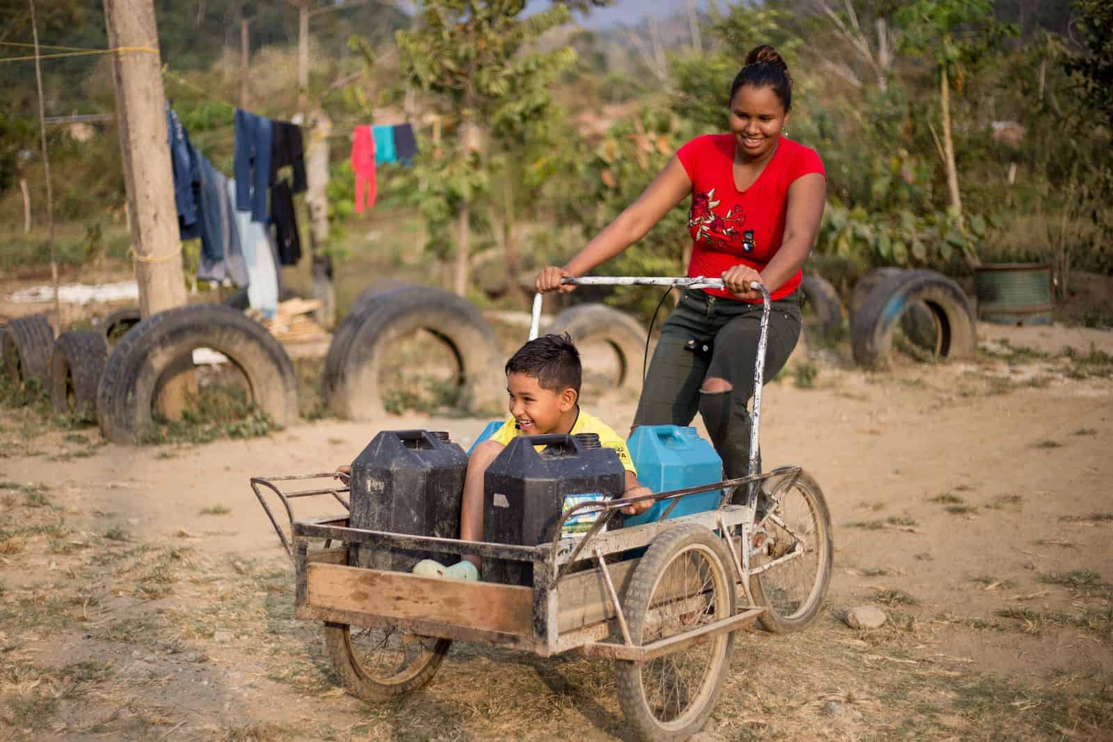 A boy rides in a tricycle cart holding water jugs, as a woman pedals.