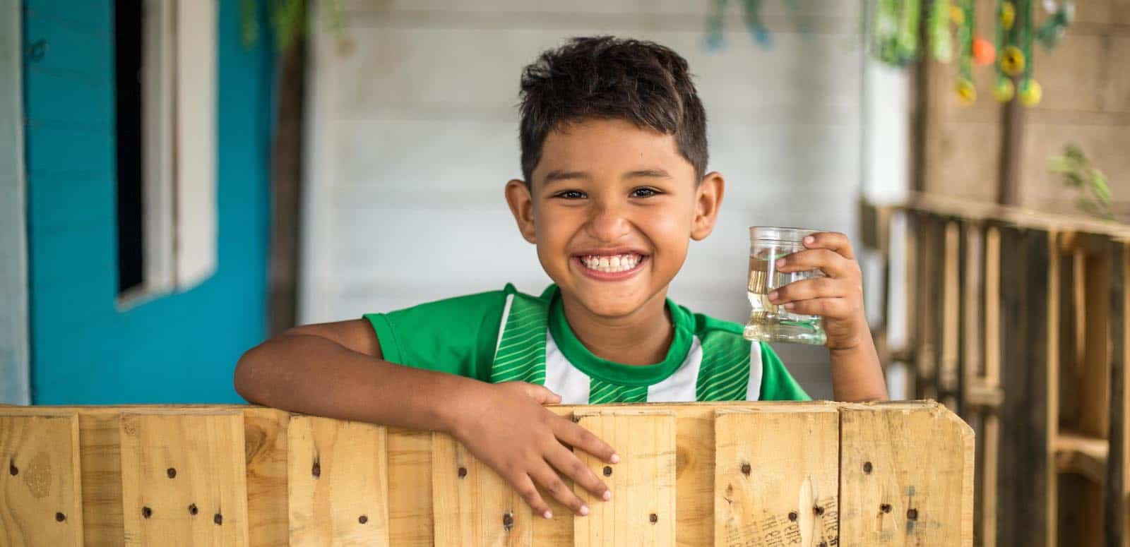 Kids Around the World: A boy stands at a fence holding a glass of water.
