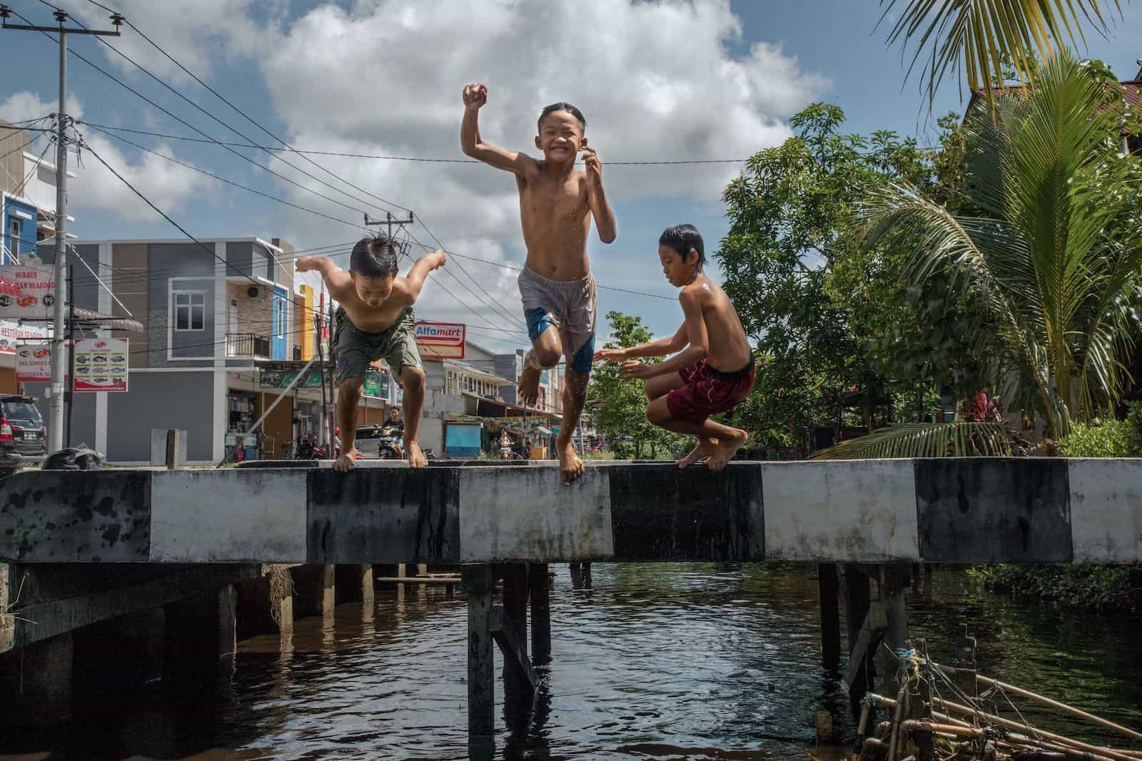 Kids Around the World: Three boys jump into a ditch next to a city block.