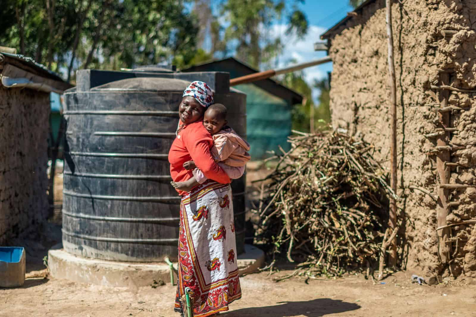 A woman with a baby on her back stands in front of a mud house with a water tank.