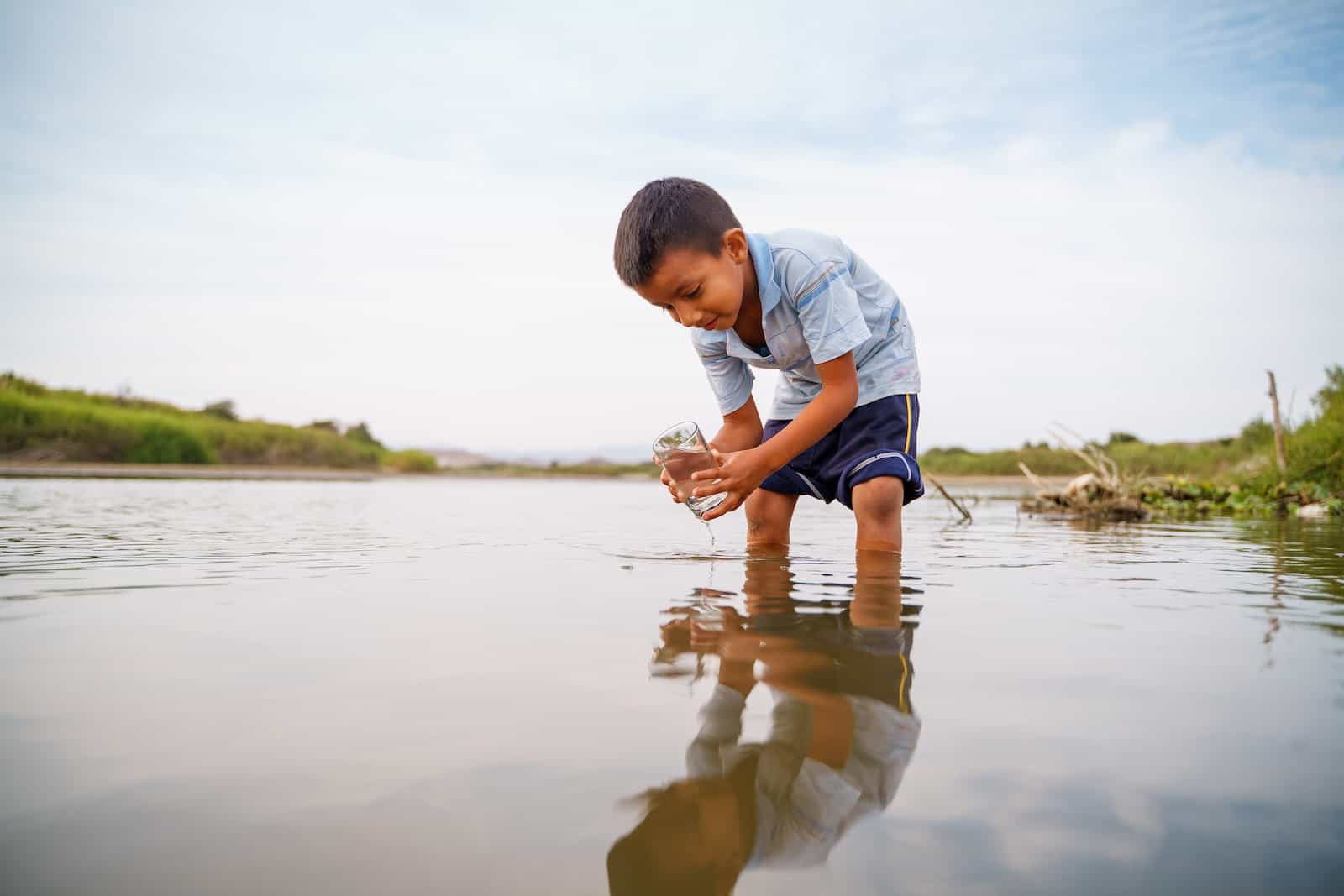 A boy leans over a river with a cup.