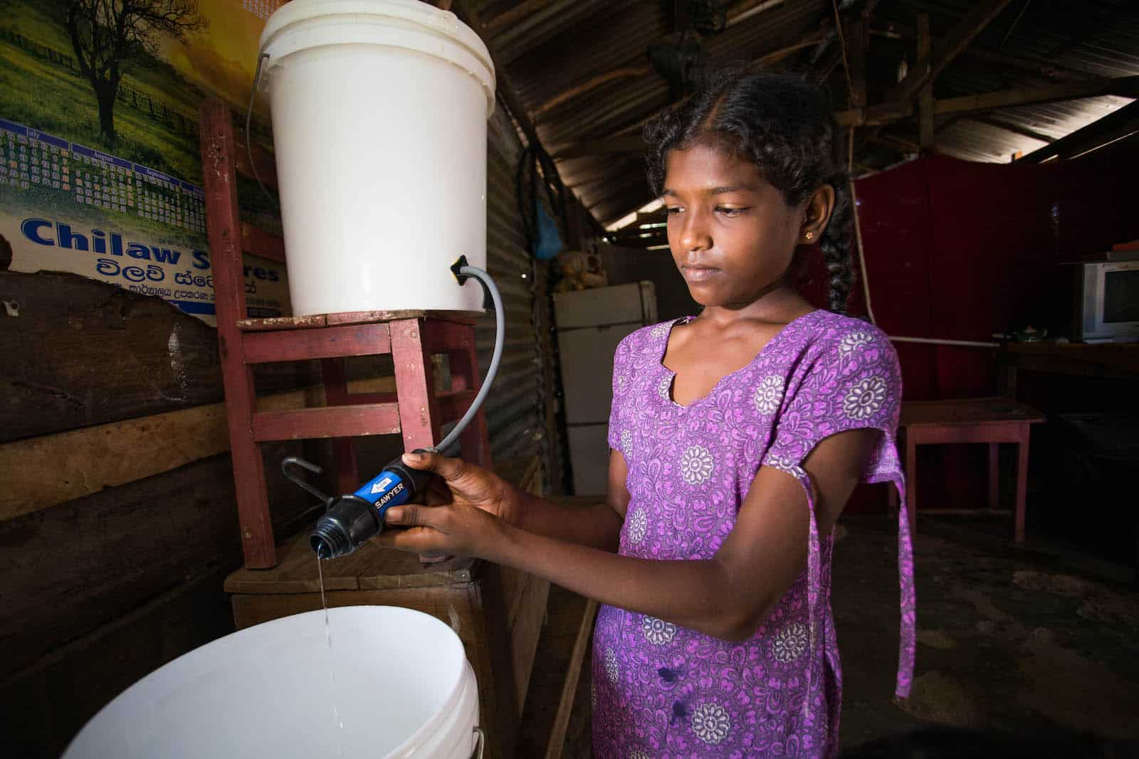 A girl in a purple shirt stands inside holding a water filter connecting one bucket to another.