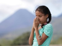 A girl in a green shirt prays, with her hands to her face.