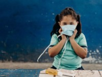 A girl wears a face mask, standing in front of a table with soap.