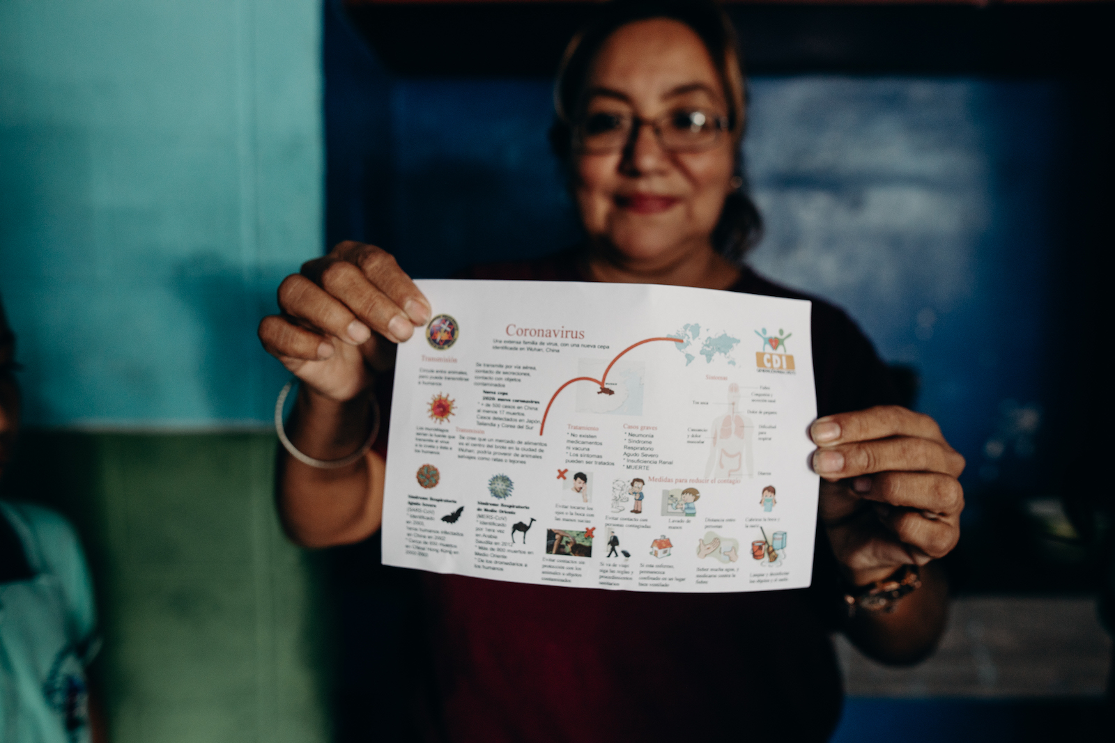 A woman holds up a sheet of paper with illustrations that says coronavirus.