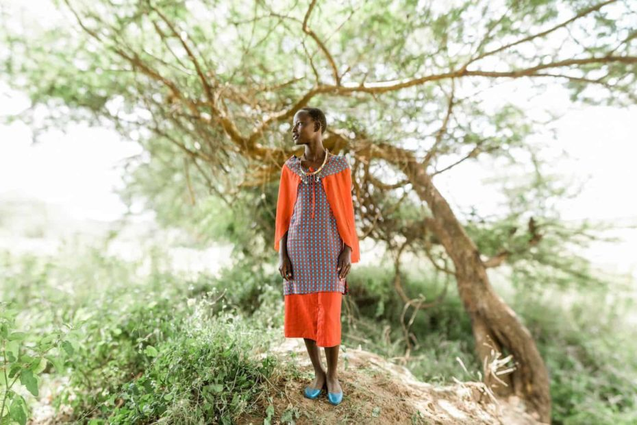 A girl in an orange dress stands in front of a leaning tree.