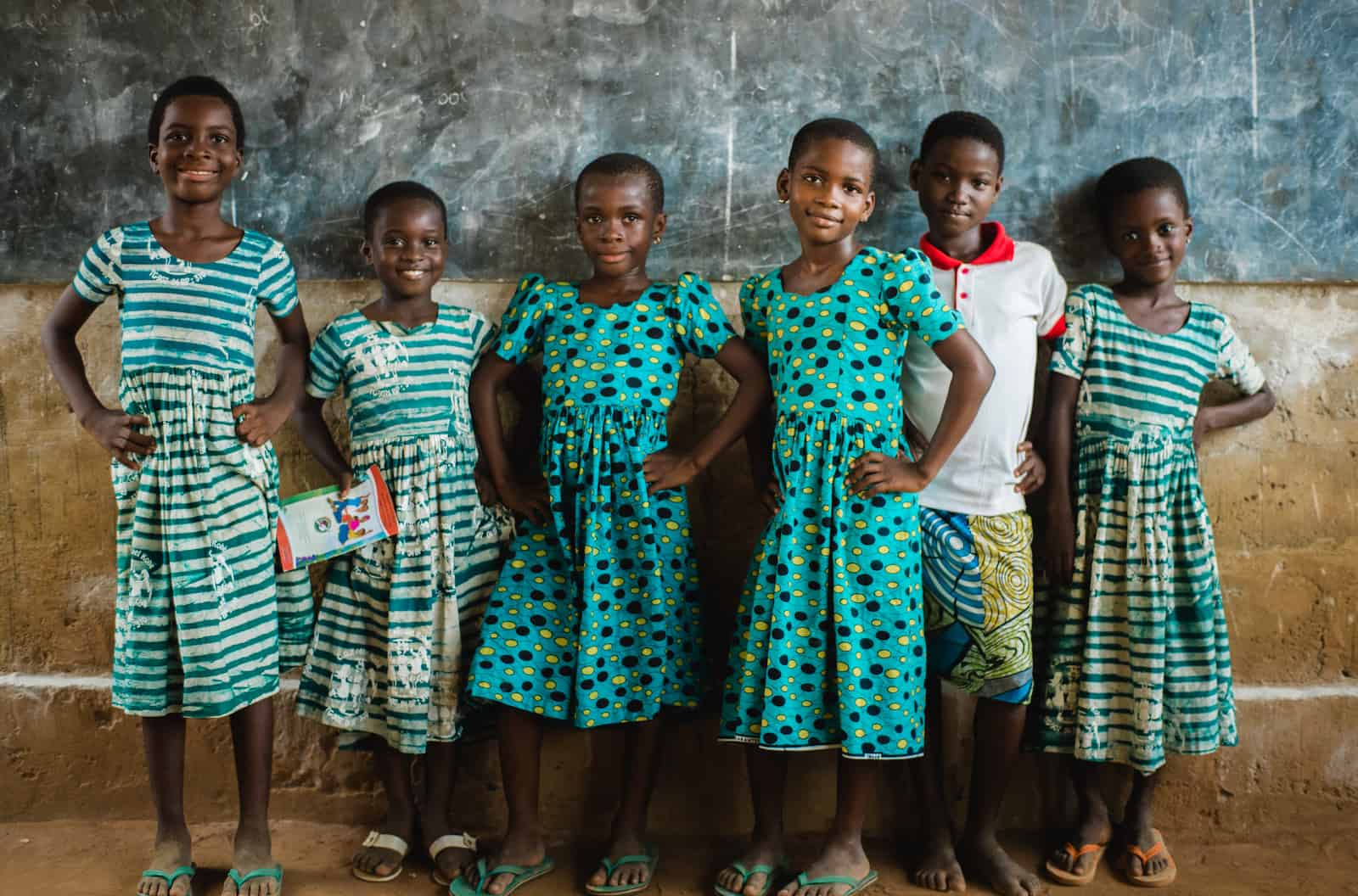 Fighting period poverty: Six girls in colorful patterned dresses stand in front of a chalkboard.