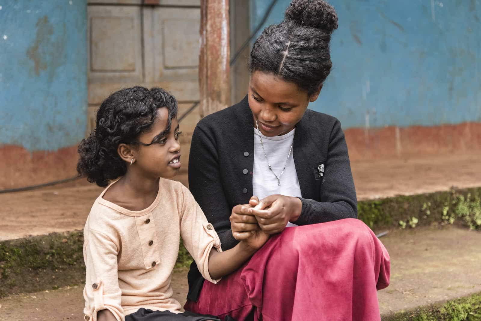 A young woman sits next to a girl, holding her hand and talking.