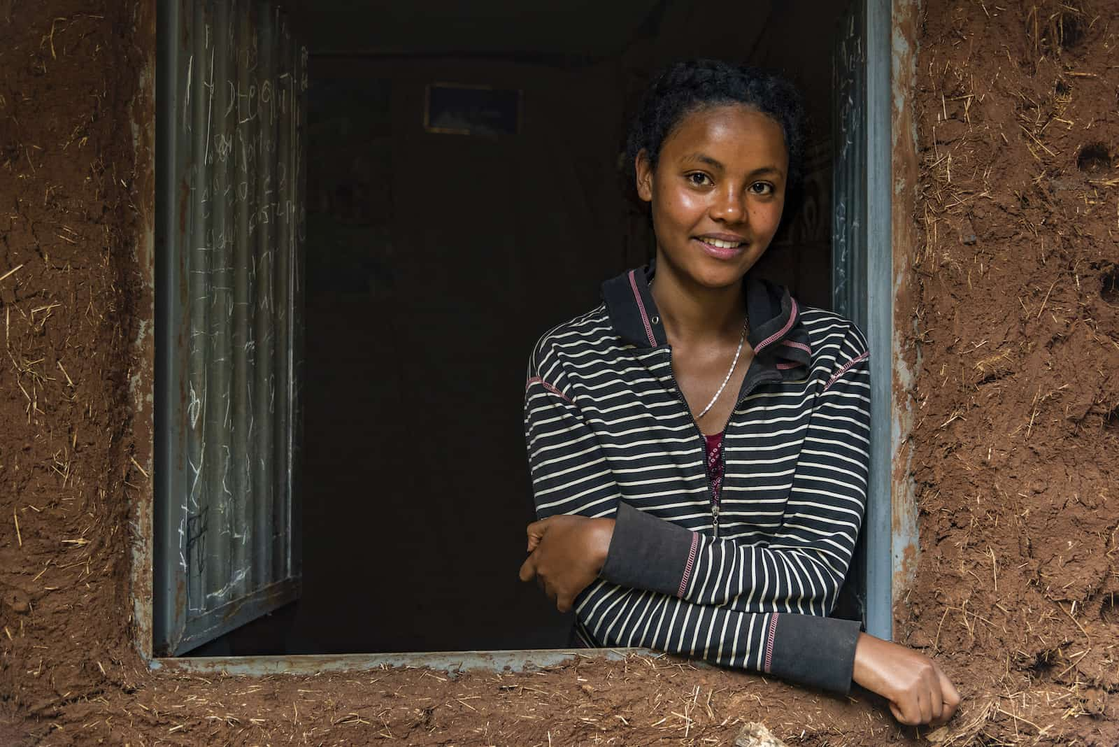 A woman stands in a window of a home made from adobe.