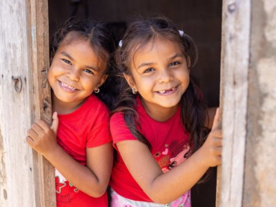 Two girls in red peek out of a door, smiling