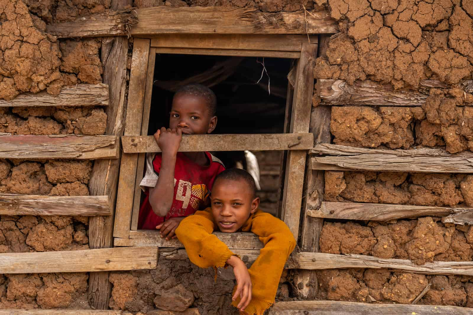 Two boys look out the window of a mud and wood home.