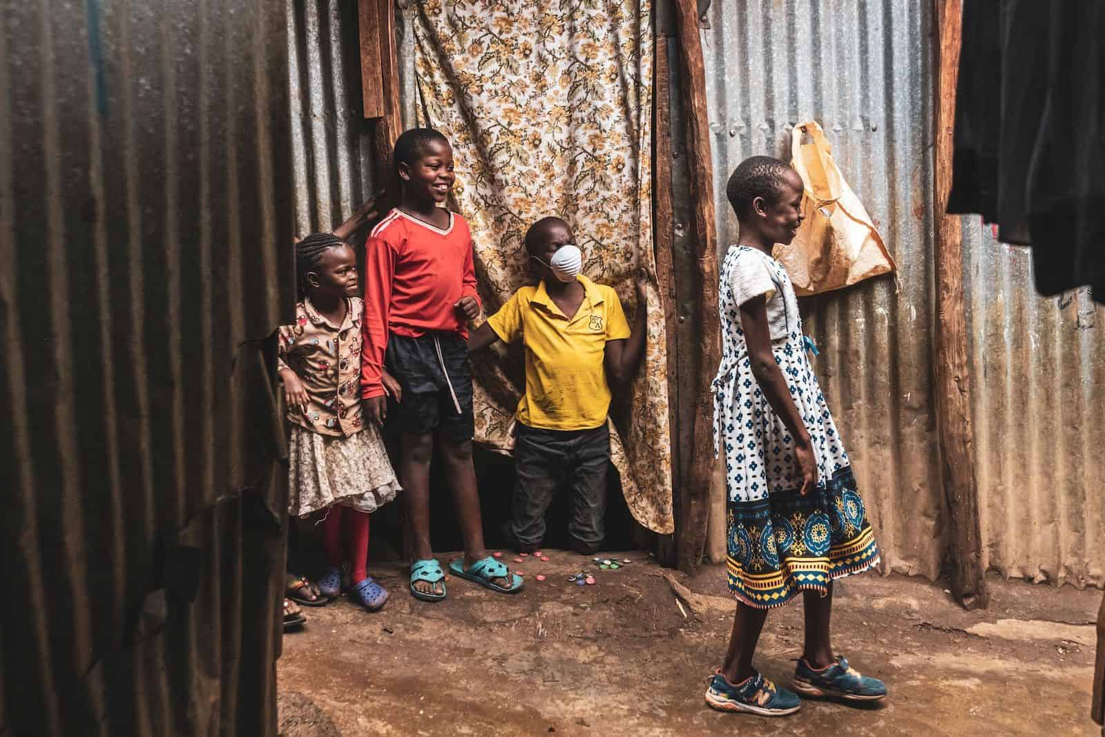 Four children stand in a slum in Kenya, where they are social distancing.