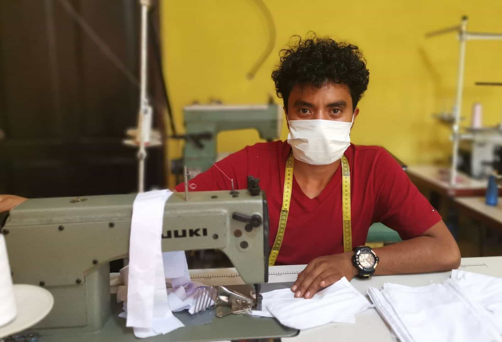 A young man sits at a sewing machine, wearing a face mask.
