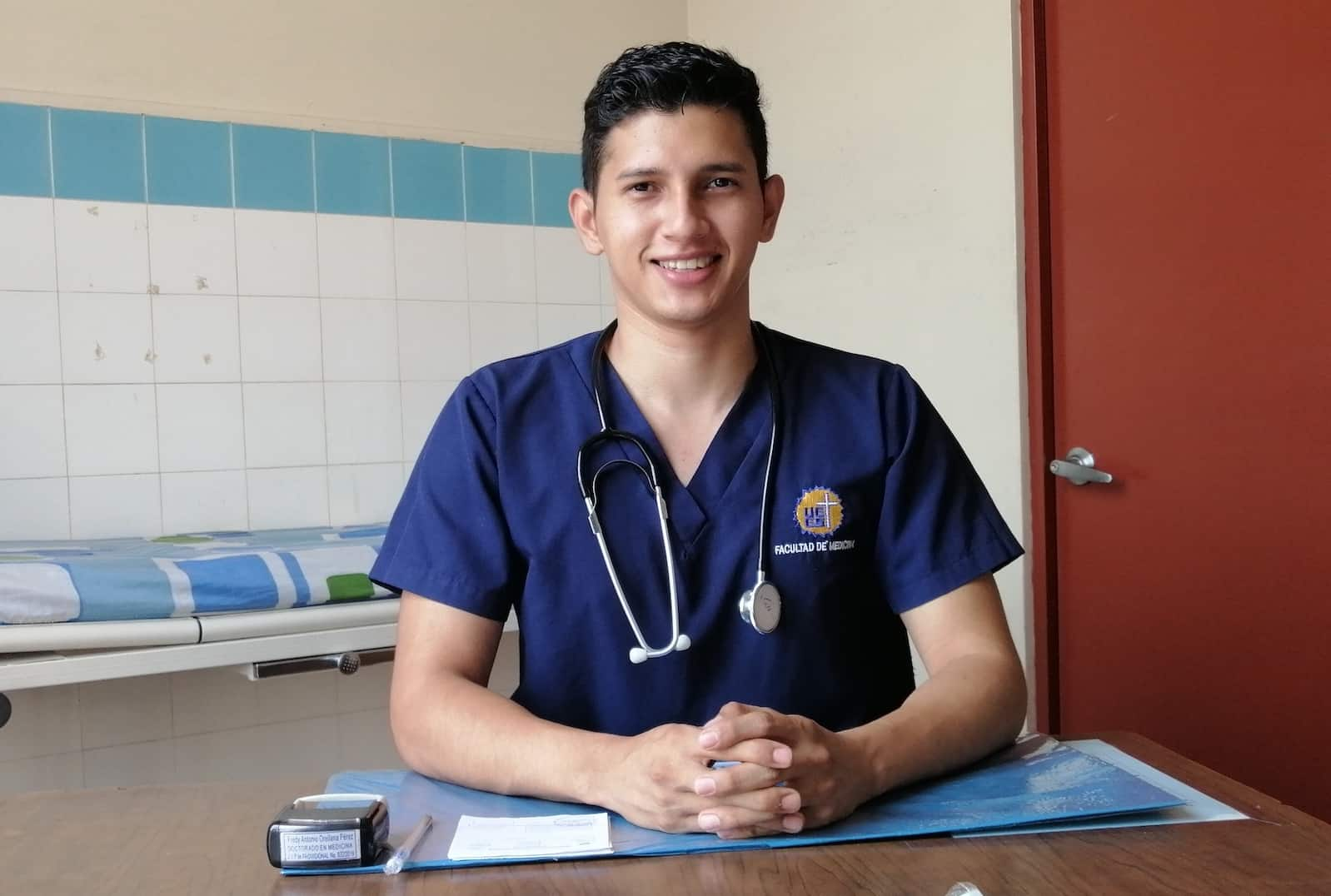 A man in scrubs with a stethoscope sits at a desk.
